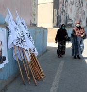 Kvinnor går förbi affischer med talibanledare i Kabul. TT NYHETSBYRÅN