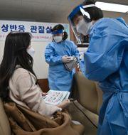 En anställd på ett äldreboende i Seoul får sin första vaccindos tidigare idag.  Jung Yeon-je / TT NYHETSBYRÅN