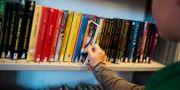 Barn lånar böcker på ett bibliotek. Arkivbild. Vilhelm Stokstad/TT / TT NYHETSBYRÅN