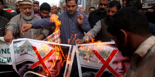 Män bränner bilder av Brenton Tarrant i Pakistan. Mohammad Sajjad / TT NYHETSBYRÅN/ NTB Scanpix