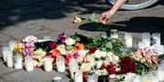 En kvinna lägger ner en ros vid minnesplatsen på Sergels väg i stadsdelen Ribersborg i Malmö där en 30-årig kvinna sköts till döds.  Johan Nilsson/TT / TT NYHETSBYRÅN