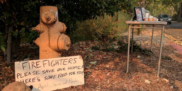 """En skylt som en evakuerad familj lämnat till brandmännen. Texten lyder: """"Snälla brandmän, rädda vårt hem! Här är lite mat till er!"""". STAFF / TT NYHETSBYRÅN"""