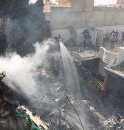 Brandmän försöker släcka elden som uppstod efter att planet kraschade. Fareed Khan / TT NYHETSBYRÅN