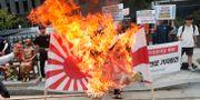Sydkoreanska demonstranter bränner en bild på Japans premiärminister samt flaggan som användes av japanska imperiet under andra världskriget. Flaggan återupptogs senare av Japans flotta.  Ahn Young-joon / TT NYHETSBYRÅN/ NTB Scanpix