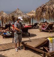 En man desinfekterar en solstrand på en grekisk strand.  ANGELOS TZORTZINIS / TT NYHETSBYRÅN