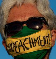 """En kvinna med texten """"avsätt"""" på sitt munskydd. Eraldo Peres / TT NYHETSBYRÅN"""