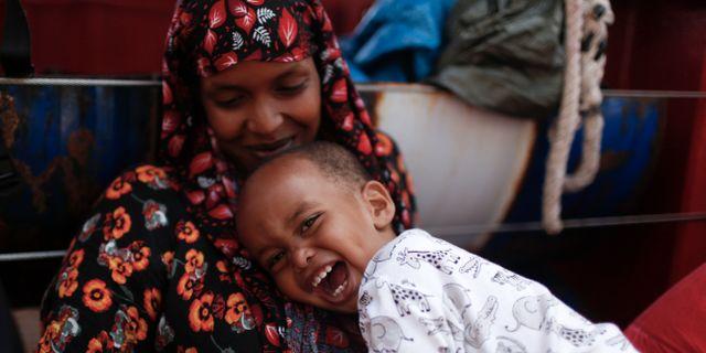 Somalisk mor med leende son i famnen efter att ha plockats upp av räddningsfartyg. Renata Brito / TT NYHETSBYRÅN