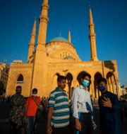 Människor i ansiktsmask firar Eid al-Adha. Hassan Ammar / TT NYHETSBYRÅN