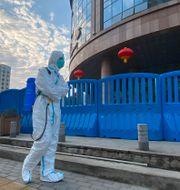 Person i skyddsdräkt i Wuhan.  Ng Han Guan / TT NYHETSBYRÅN