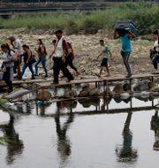 Venezuelanska flyktingar på väg in i Colombia. Fernando Vergara / TT NYHETSBYRÅN