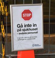 En skylt varnar för corona och uppmanar patienter att inte gå in i sjukhuset vid enten till Centralsjukhuset i Karlstad i Värmland Fredrik Sandberg/TT / TT NYHETSBYRÅN