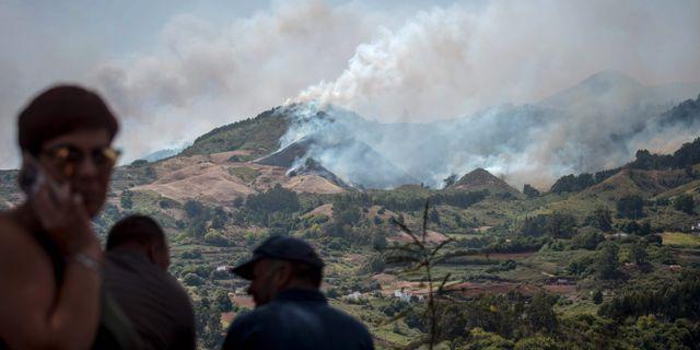 Invånare blickar ut mot brandens om härjar ön Gran Canaria. DESIREE MARTIN / AFP