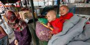 Två barn vilar vid ett matstånd i  regionen Xinjiang. Eugene Hoshiko / TT / NTB Scanpix