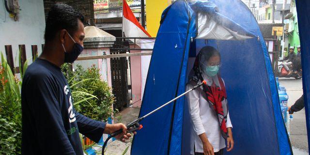En kvinna desinfekteras i Malang i östra Javaprovinsen i Indonesien. ANTARA FOTO / TT NYHETSBYRÅN