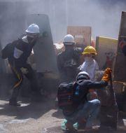 Demonstranter skyddar sig med sköldar mot militären i Myanmar. TT NYHETSBYRÅN
