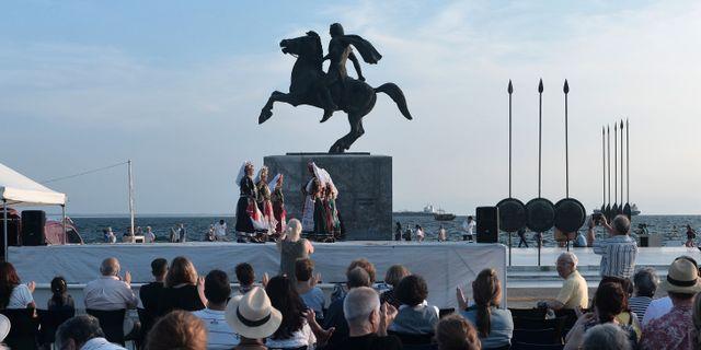 Dansare i traditionella kläder framför en staty av Alexander den store i Thessaloniki, Grekland.  SAKIS MITROLIDIS / AFP