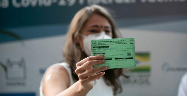 En sjukvårdare i Brasilien visar sitt vaccinationskort Bruna Prado / TT NYHETSBYRÅN