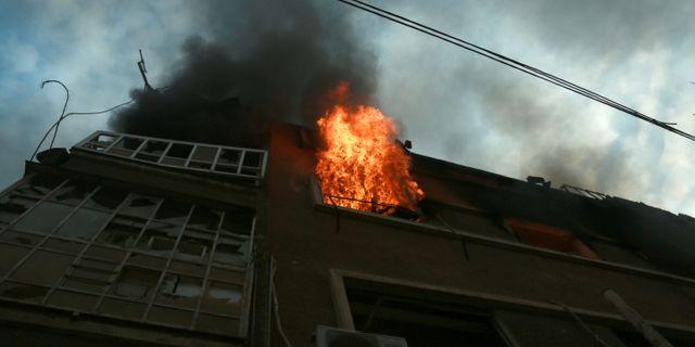 Eldlågor slår ut från en kontorsbyggnad i Douma. HAMZA AL-AJWEH / AFP
