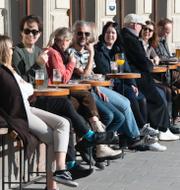 personer på en uteservering i Gamla stan i Stockholm och Ulf Kristersson.  TT