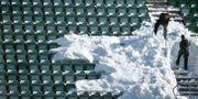 Funktionärer skottar bort snö från läktaren under måndagen inför den allsvenska premiärmatchen mellan GIF Sundsvall och Örebro SK på Idrottsparken, Sundsvall, 2 april. Erik Mårtensson/TT / TT NYHETSBYRÅN