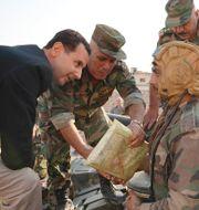 Syriens president Bashar al-Assad pratar med militärer. Arkivbild. TT NYHETSBYRÅN
