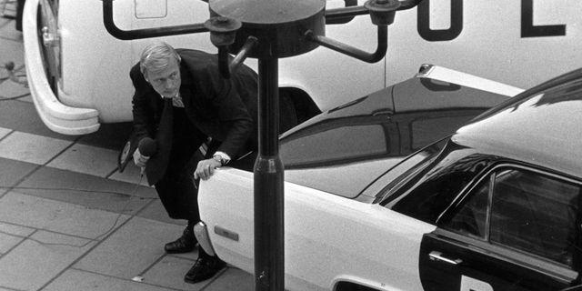 Bo Holmström duckar bakom en bil under Norrmalmstorgsdramat PRESSENS BILD
