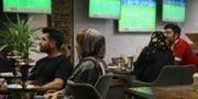 Människor följer en fotbollsmatch från ett café i Teheran. WANA NEWS AGENCY / TT NYHETSBYRÅN