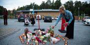 Människor samlas under söndagskvällen på platsen i Botkyrka där den 12-åriga flickan sköts till döds. Ali Lorestani/TT / TT NYHETSBYRÅN