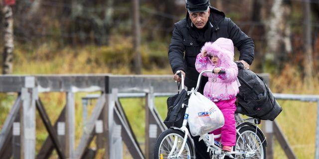 Arkivbild, 2015, en liten flicka får hjälp på cykel över gränsen. NTB SCANPIX / TT NYHETSBYRÅN