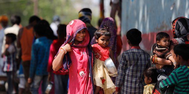 Kvinna och barn i kö för att ta emot mat.  Rajesh Kumar Singh / TT NYHETSBYRÅN