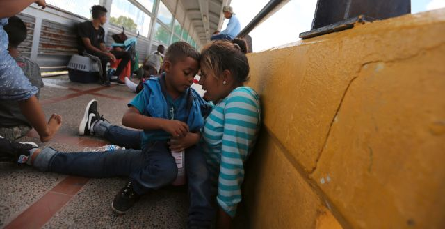 En kvinna och hennes barn vid gränsen mellan USA och Mexiko.  Fernando Llano / TT NYHETSBYRÅN