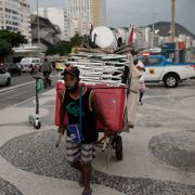 Vendor Andre Luiz hauls his beach chairs from Copacabana Beach amid the new coronavirus pandemic in Rio de Janeiro, Brazil, Friday, March 5, 2021. New measures took effect on Friday, aiming to halt the spread of COVID-19. Silvia Izquierdo / TT NYHETSBYRÅN