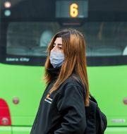 Kvinna med munskydd vid en lokalbuss i Lund. Claudio Bresciani / TT / TT NYHETSBYRÅN