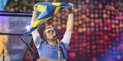Chris Martin håller upp en Sverige-flagga under konserten på Ullevi.  Björn Larsson Rosvall/TT