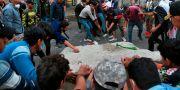 Irakiska demonstranter slår sönder en bit av den cementmur som skulle hålla dig borta från Ahrar-bron i centrala Bagdad. Khalid Mohammed / TT NYHETSBYRÅN