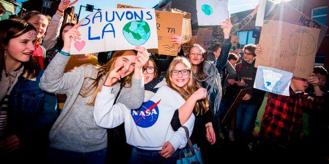 """Elever håller upp skyltar med budskapet att """"rädda planeten"""". JASPER JACOBS / BELGA"""