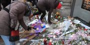 Människor lämnar blommor för att hedra offren för dådet PATRICK HERTZOG / AFP