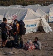 Personer i ett läger för migranter och flyktingar i Grekland. Petros Giannakouris / TT NYHETSBYRÅN
