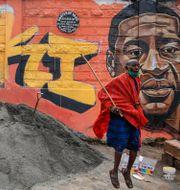En man framför en väggmålning föreställande George Floyd.  Brian Inganga / TT NYHETSBYRÅN