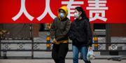 Människor i ansiktsmask i Peking.  Mark Schiefelbein / TT NYHETSBYRÅN