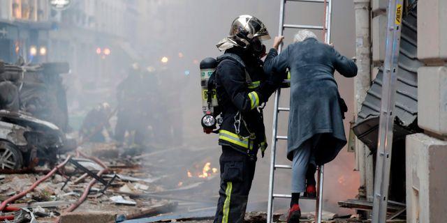 En boende i huset får hjälp att evakuera. THOMAS SAMSON / AFP