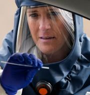 En kvinna i skyddskläder genomför ett coronatest på en person i en bil.  Rick Bowmer / TT NYHETSBYRÅN