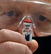 Storbritanniens premiärminister Boris Johnson med Astra Zenecas vaccinkandidat AZD1222. Paul Ellis / TT NYHETSBYRÅN