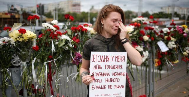 """Alina Krus, 26, med ett plakat som enligt AP:s översättning lyder: """"Det är min födelsedag i dag. Jag önskade att ingen skulle dödas. Vi är ett fredligt folk. Sluta med våldet, snälla"""". TT NYHETSBYRÅN"""
