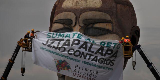 """Illustrationsbild: En gigantisk mask med texten """"Anslut dig till Iztapalapa-utmaingen. Noll smittsamhet"""" hängs upp på Cabeza de Juarez-museet i Iztapalapa i Mexico City.  Marco Ugarte / TT NYHETSBYRÅN"""