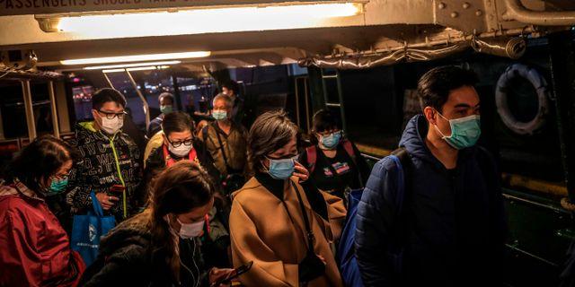 Människor med ansiktsmasker som skydd mot virussmitta i Hongkong. VIVEK PRAKASH / TT NYHETSBYRÅN