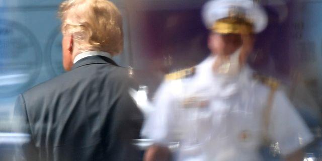 Donald Trump och en soldat reflekteras i en glasruta vid toppmötet i Bryssel. Geert Vanden Wijngaert / TT / NTB Scanpix