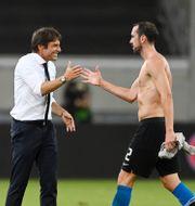 Inters huvudtränare Antonio Conte ler mot spelaren Diego Godin.  Sascha Steinbach / TT NYHETSBYRÅN