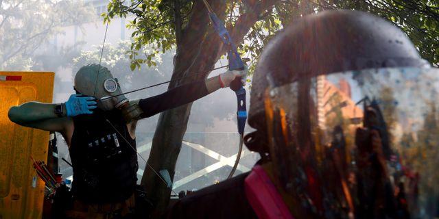 Bågskyttar förekommer på aktivisternas sida. Under morgonen skadades en polis av en pil. ATHIT PERAWONGMETHA / TT NYHETSBYRÅN