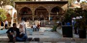 Människor sitter utanför en moské i Damaskus. Arkivbild från den 19 juni i år. YAMAM AL SHAAR / TT NYHETSBYRÅN